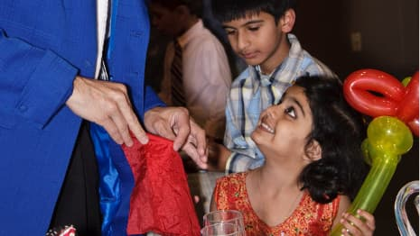 Magician with red silk performs close up magic for a young boy and girl during a Chicago area event!.