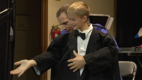 A a young boy in a magician's tux performs some amazingly funny magic tricks!
