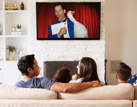 A family in their living room, watching pre-recorded personalized virtual Magic Show!